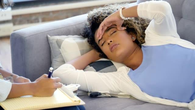 vídeos y material grabado en eventos de stock de angustiada mujer joven expresa emociones durante la sesión de terapia - acostado
