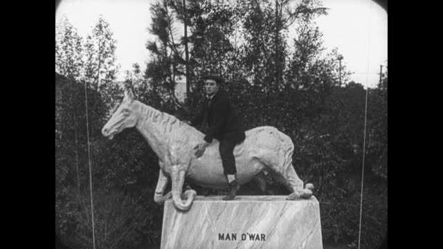 1921 distressed artist watches as man (buster keaton) hiding from police destroys his horse statute - 1921 stock videos & royalty-free footage