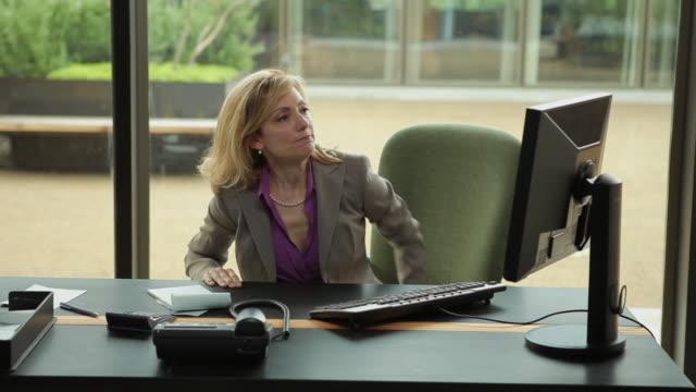MS Distressed businesswoman calming down at desk / Portland, Oregon, USA