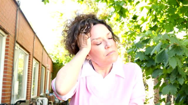 Verontruste volwassen Kaukasische vrouwelijke lijden een hoofdpijn op haar balkon 4k