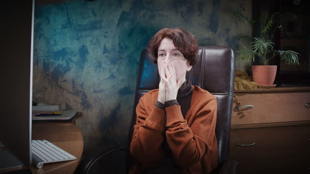 distressed mature woman is rubbing her face while sitting at the computer at home office - mature women stock videos & royalty-free footage