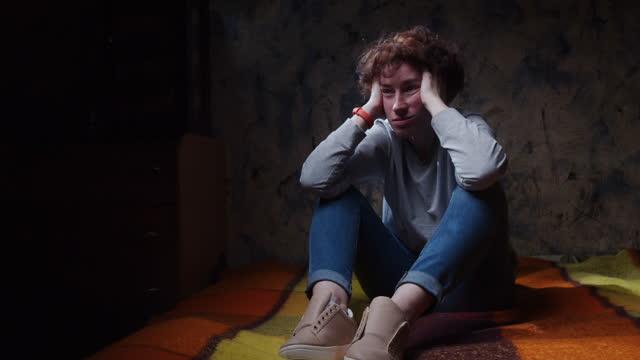 beunruhigte frau sitzt und hält ihren kopf in der hand auf dem sofa in dunklen raum - one mature woman only stock-videos und b-roll-filmmaterial