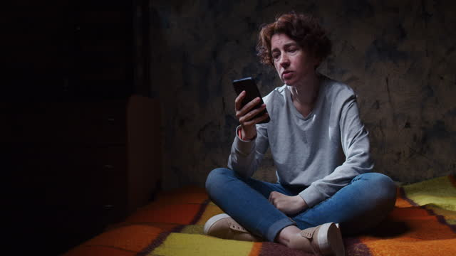 distressed woman is sitting on the sofa in dark room and holding phone in apathy - one mature woman only stock videos & royalty-free footage