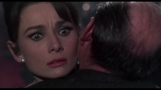 1963 Distressed woman (Audrey Hepburn) struggles to get away from threatening man during party game