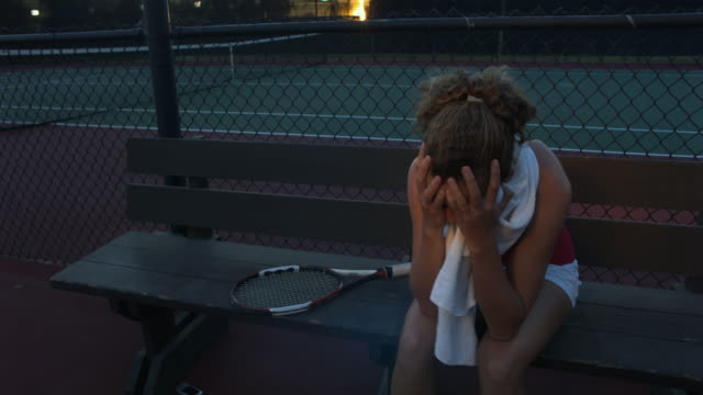 ms, distressed young woman sitting on bench at tennis court, santa barbara, california, usa - attività del fine settimana video stock e b–roll