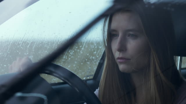 Distressed young woman through rainy windscreen
