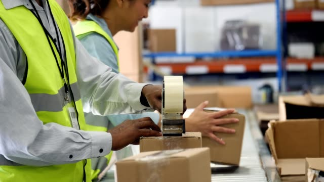 Distribution warehouse employees prepare packages to be sent to customers