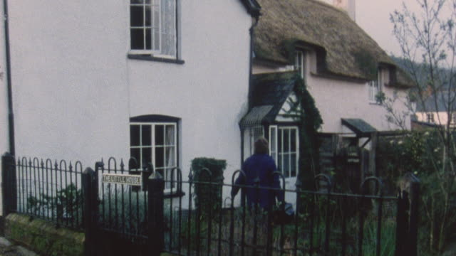 1983 montage district nurse carrying bag walking up lane, entering home, and attending to bandage on elderly patient's arm / porlock, somerset, england - bandage stock videos & royalty-free footage