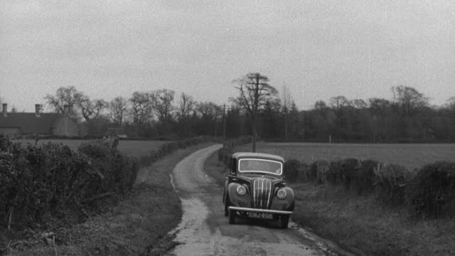 1952 MONTAGE District nurse getting in to vehicle, driving down country lane, stopping for cattle crossing lane, and farmer tipping his hat / Wadhurst, England, United Kingdom