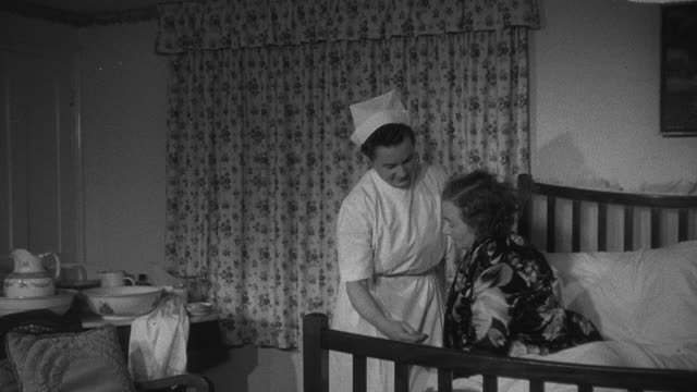 1952 montage district nurse on house call assisting patient out of bed and into chair, patient sitting in chair talking, and nurse making patient's bed / wadhurst, england, united kingdom - wadhurst stock videos & royalty-free footage
