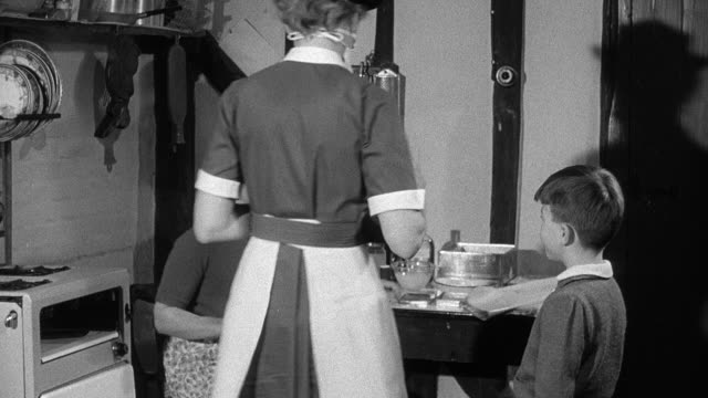 1952 montage district nurse on house call donning a surgical mask and treating resident's injured arm in the kitchen while child observes the procedure / wadhurst, england, united kingdom - wadhurst stock videos & royalty-free footage