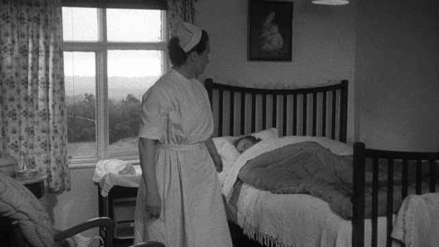1952 montage district nurse on house call opening curtains in sleeping patient's bedroom, descending stairs in to kitchen, and leaving note for exhausted expectant father asleep at kitchen table / wadhurst, england, united kingdom - wadhurst stock videos & royalty-free footage