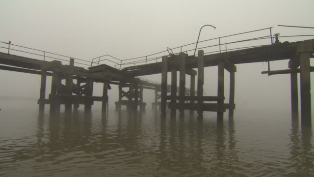 vídeos de stock e filmes b-roll de a disused pier extending into fog-covered water is approached by boat, river medway, kent, uk. - pontão