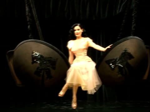 vídeos de stock, filmes e b-roll de dita von teese posing at photocall and interview black velvet curtain drawn aside as reveals dita posing on stage on swing in shape of giant bra... - dita von teese