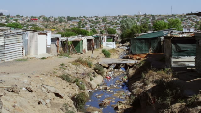 vidéos et rushes de ws ditch between houses and shacks in town / diepsloot, south africa - cahute