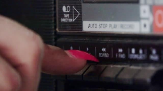 dito preme su tasto play di un vecchio registratore a cassette