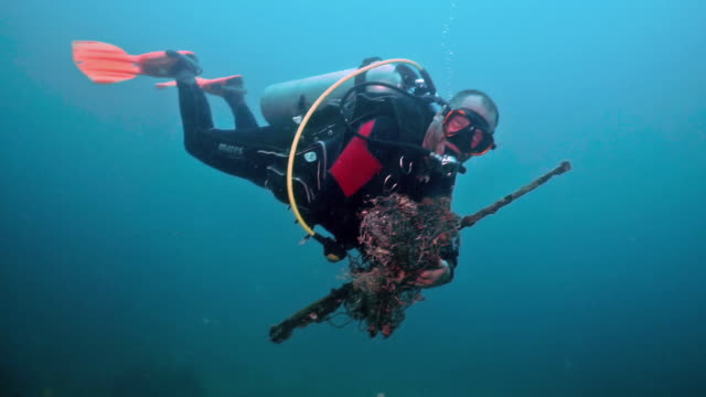 vídeos de stock, filmes e b-roll de dive against debris underwater scuba diver eco tourist volunteer on environmental cleanup removing discarded fishing net pollution from sea - eco tourism