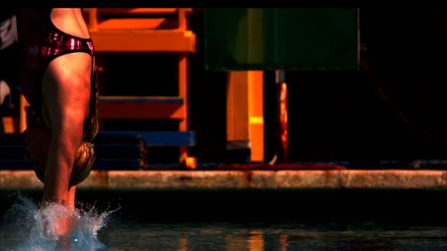 vídeos de stock, filmes e b-roll de a diver enters the water hands first. - tensão de superfície