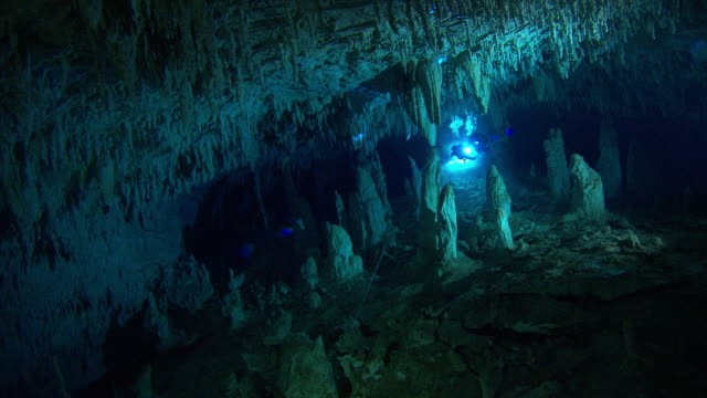 diver explore an amazing underwater cave with stalactites and stalagmites. available in hd. - バハマ点の映像素材/bロール