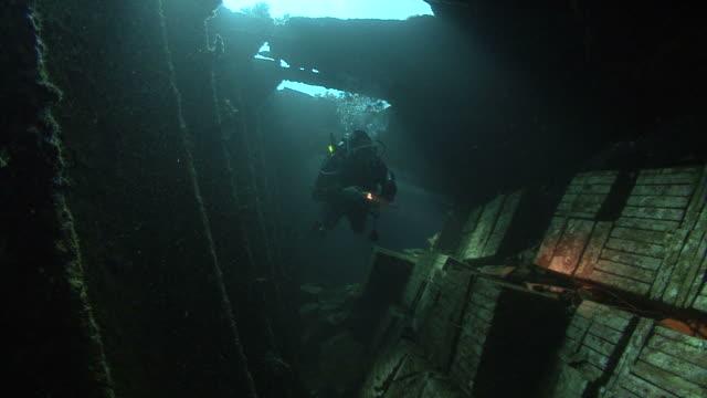 diver iniside Kingston wreck, shows tiles, Red sea, Egypt