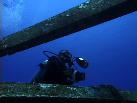 diver inspecting sunken wreckage - tauchgerät stock-videos und b-roll-filmmaterial