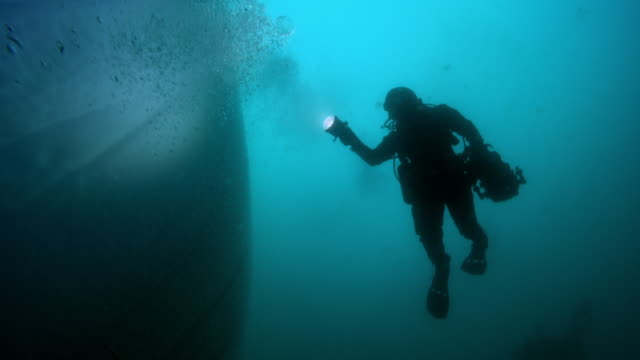 stockvideo's en b-roll-footage met diver inspects underside of an iceberg - onder