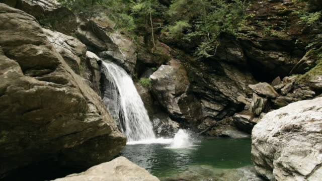 ws diver jumping over a waterfall into water / stowe, vermont, united states - stowe vermont stock videos & royalty-free footage