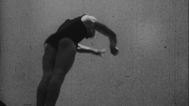 a diver jumps into the water at the 1936 olympics - 1936 stock-videos und b-roll-filmmaterial