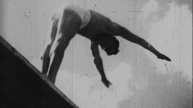 stockvideo's en b-roll-footage met diver jumps into the water at the 1936 olympics - 1936