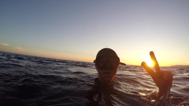 vídeos de stock e filmes b-roll de pov diver making peace hand gesture in water at sunset - gesticular