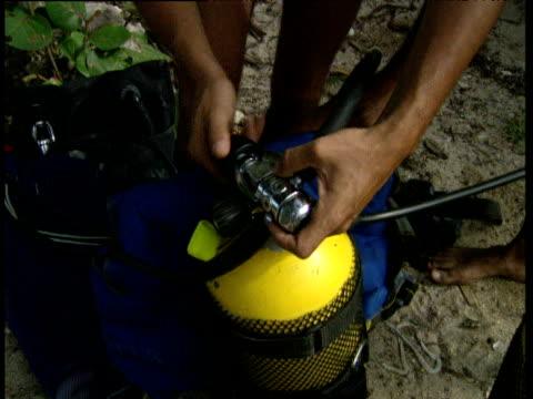 stockvideo's en b-roll-footage met diver prepares oxygen tanks trinidad and tobago - duikfles