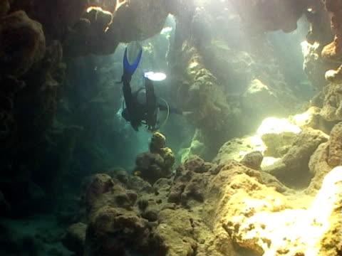 diver ws swimming through rocks - tauchgerät stock-videos und b-roll-filmmaterial