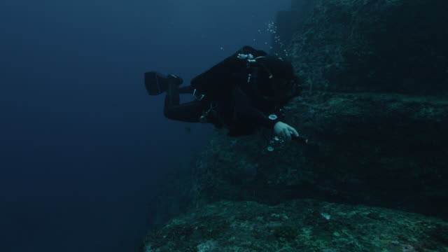 Diver swims over ledges of Yonaguni monument. Japan