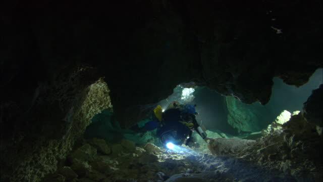 a scuba diver swims through an underwater cave. - gefahr stock-videos und b-roll-filmmaterial