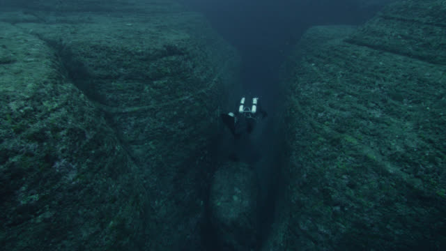 diver swims through crevice near yonaguni monument. japan - monument stock videos & royalty-free footage