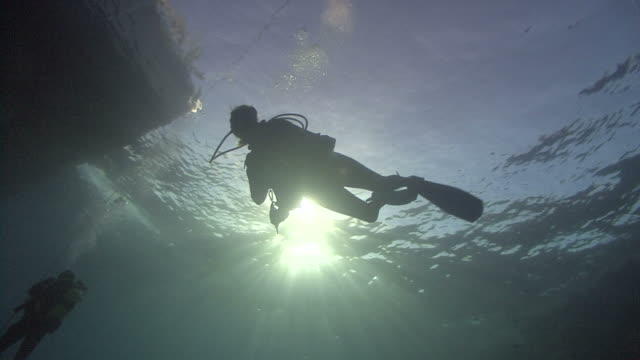 diver under boat in sunlight, Red sea. Egypt