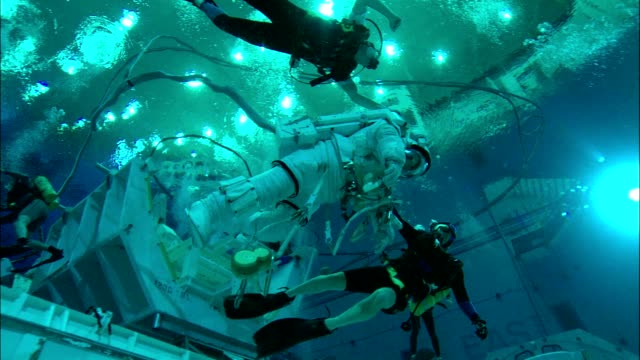 divers carry an astronaut underwater at the neutral buoyancy lab. - astronaut stock videos & royalty-free footage