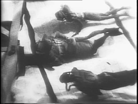 vídeos de stock, filmes e b-roll de divers in full wet suit gear paddling a small rubber raft / divers moving from the raft in to the water / divers swimming around the bottom of a pool... - diving suit