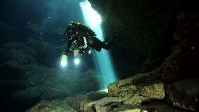 divers inside a cave with light in pianosa island - electric torch stock videos & royalty-free footage