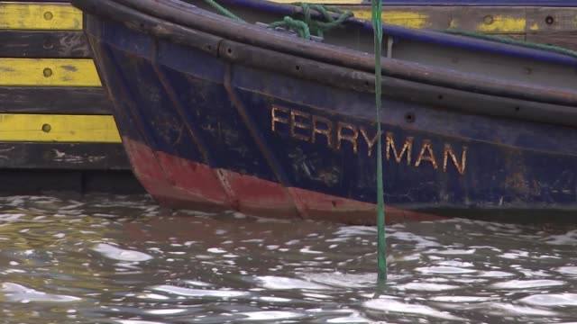 Divers search for unexploded World War 2 bombs in River Thames Crane pulling tyres from water to cheers from diving team Diver into water