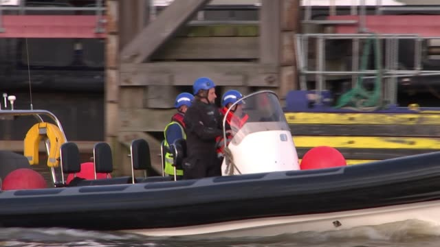 Divers search for unexploded World War 2 bombs in River Thames ENGLAND London EXT Dive superviser Joe Bamblett down steps to rig and onto boat Boat...