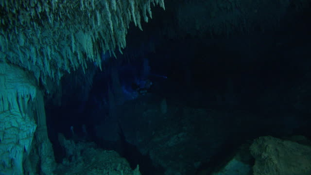 divers swim through a dark underwater cave filled with stalactites and stalagmites. available in hd. - バハマ点の映像素材/bロール