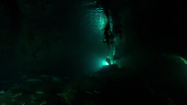vídeos de stock, filmes e b-roll de divers use flashlights to explore a dark underwater cave. available in hd. - lanterna elétrica