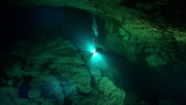 divers use flashlights to explore a dark underwater cave. available in hd. - バハマ点の映像素材/bロール