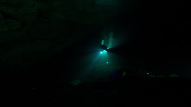 vídeos de stock, filmes e b-roll de divers use flashlights to explore dark underwater caves. available in hd. - lanterna elétrica