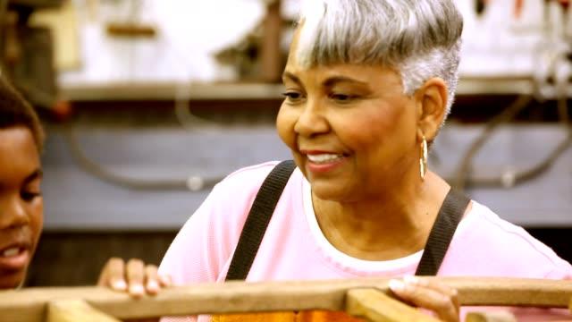 vídeos de stock, filmes e b-roll de diverso neto active seniors-africano descida, ajudando na oficina - artesão