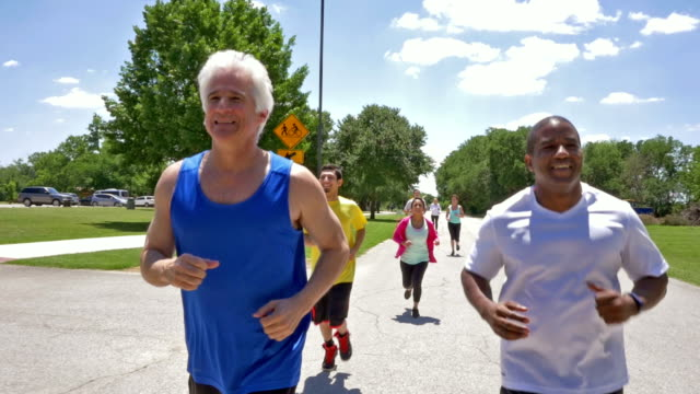 Diverse adults training for marathon or 5k race together outdoors