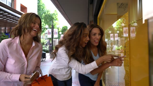 diverse beautiful friends looking at a retail display while laughing and having a great time - retail display stock videos & royalty-free footage
