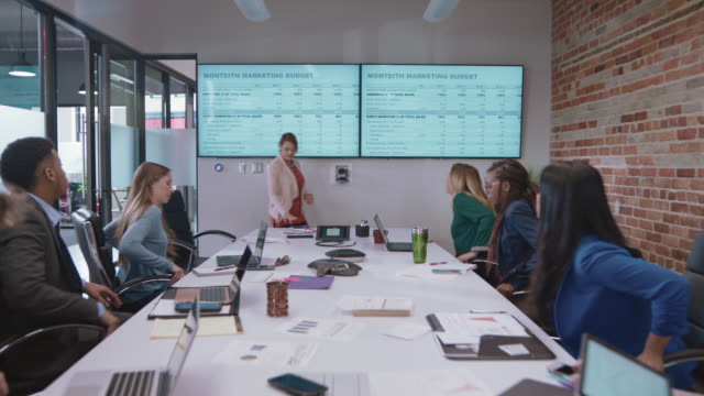 diverse business partners sit down at conference table to begin a team business meeting in a corporate board room - learning video stock e b–roll