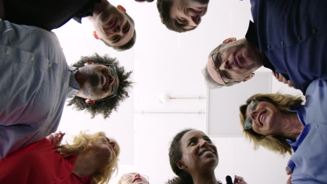 stockvideo's en b-roll-footage met divers business team in een huddle - laag camerastandpunt